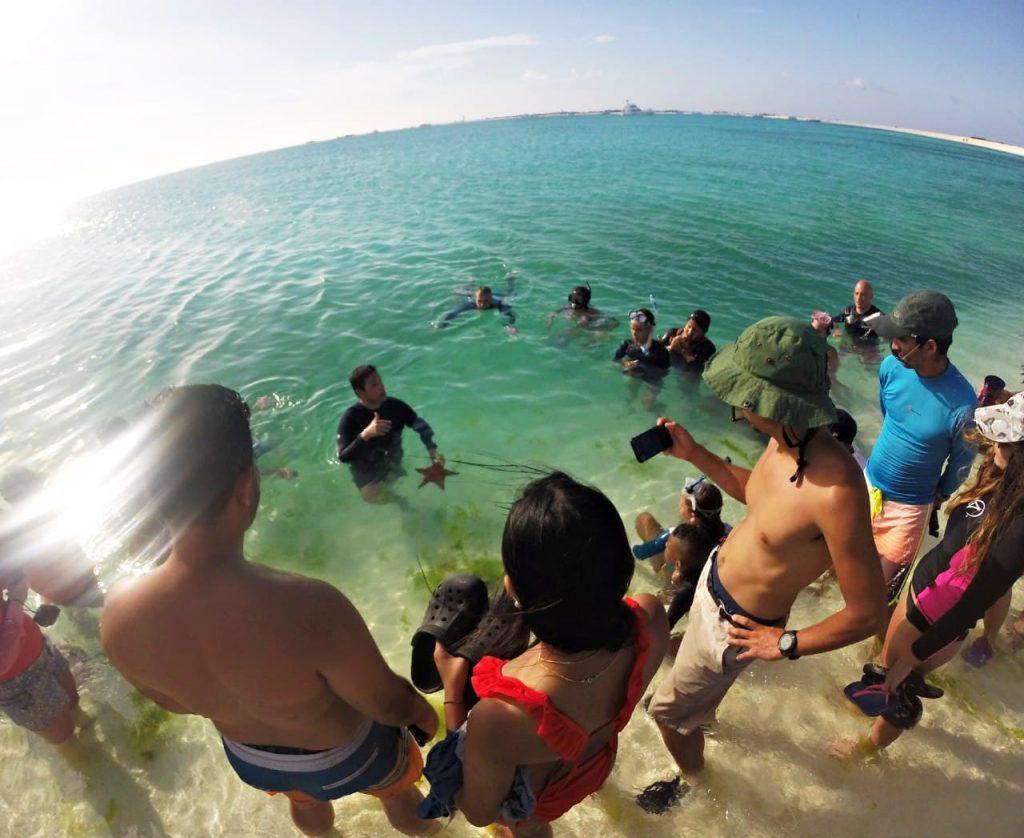 Drai Cabello explicando la importancia de las estrellas de mar a los turistas en La Tortuga